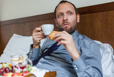 Businessman during breakfast. He is lying on bed. Stock Photos