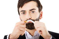 Businessman breaking a cigarette. Royalty Free Stock Images