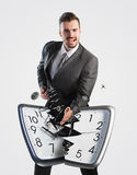 Businessman breaking a clock Stock Photography
