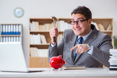The businessman breaking piggybank in the office Stock Photo