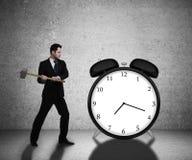 Businessman breaks clock Stock Photos