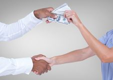 Businessman bribing partner while shaking handsagainst grey background Royalty Free Stock Photography