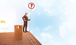 Businessman on brick house roof showing banner with question mark. Mixed media Royalty Free Stock Images