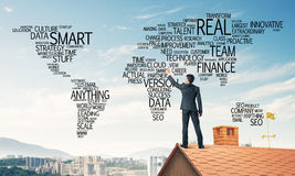 Businessman on brick roof draw world map as concept of globaliza Stock Photography