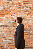 Businessman by brick wall Stock Image