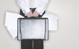 Businessman with briefcase. Businessman Standing with his briefcase stuffed full of papers Stock Image