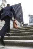 Businessman With Briefcase Ascending Steps. Full length rear view of a businessman with briefcase ascending steps Royalty Free Stock Photos