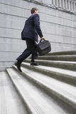 Businessman With Briefcase Ascending Steps. Full length side view of a businessman with briefcase ascending steps Royalty Free Stock Photo