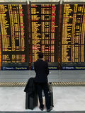 Businessman with a briefcase on a background of departure board at airport.  royalty free stock photography