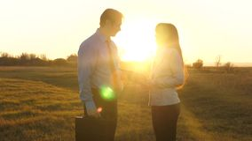 Businessman with a briefcase and business woman business meeting in a park. Teamwork of business partners in the sunset
