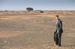 Businessman with a briefcase in  a desert village Royalty Free Stock Image