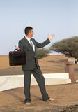 Businessman with a briefcase in  a desert village Stock Images