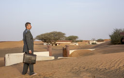 Businessman with a briefcase in  a desert village Royalty Free Stock Photos