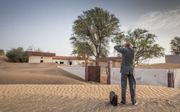 Businessman with a briefcase in  a desert village Stock Photo