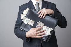 Businessman with a briefcase full of money in the hands of Stock Photo
