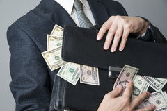 Businessman with a briefcase full of money in the hands of Royalty Free Stock Photos