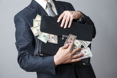 Businessman with a briefcase full of money in the hands of Stock Image