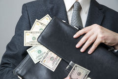 Businessman with a briefcase full of money in the hands of Stock Photography