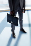 Businessman with briefcase. Briefcase in hand of businessman in elegant suit royalty free stock photography