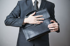 Businessman with briefcase in hand Stock Images