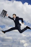 A businessman with briefcase, leaping in the air Stock Image
