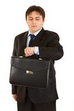 Businessman with briefcase looking at his watch Stock Photos