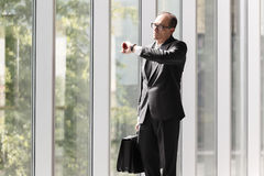 Businessman with briefcase looking at his watch Stock Image