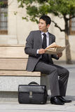 Businessman with briefcase and newspaper on park bench, looking over shoulder Stock Photo