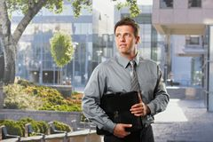 Businessman with briefcase outside office Stock Photos