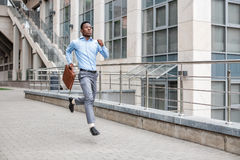 Businessman with briefcase running Stock Images