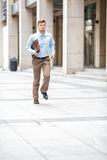 Businessman with  briefcase running. Young businessman with a briefcase running in a city street. Hurrying to work Royalty Free Stock Photography