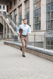 Businessman with a briefcase running. Young businessman with a briefcase running in a city street. Hurrying to work Stock Image