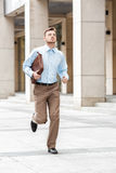 Businessman with  briefcase running. Young businessman with a briefcase running in a city street. Hurrying to work Royalty Free Stock Photo