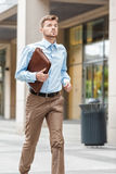 Businessman with  briefcase running. Young businessman with a briefcase running in a city street. Hurrying to work Stock Images