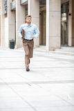 Businessman with  briefcase running. Young businessman with a briefcase running in a city street. Hurrying to work Stock Photography