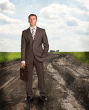 Businessman with briefcase standing on the road Royalty Free Stock Images