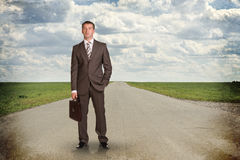 Businessman with briefcase standing on the road Stock Photography