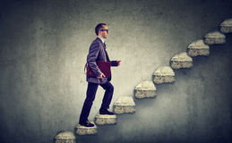 Businessman with briefcase stepping up a stairway career ladder royalty free stock photography