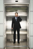 Businessman With Briefcase Using Cellphone In Elevator Royalty Free Stock Photo