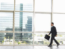 Businessman With Briefcase Walking In Office Royalty Free Stock Photo