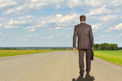 Businessman with briefcase walking on road ahead. Royalty Free Stock Image