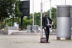 Businessman with briefcase wearing a gas mask outdoor. Businessman stay on the street with briefcase wearing a gas mask outdoor Stock Image