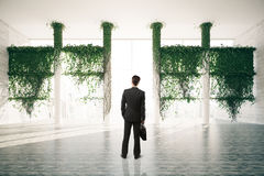 Businessman in bright interior with plants. Businessman standing in beautiful bright room interior with plants growing all over columns and city view with Stock Photo