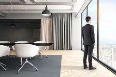 Businessman in bright meeting room. Side view of thoughtful young businessman standing in bright meeting room interior with furniture, curtains and city view stock photos