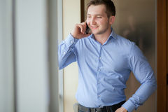 Businessman in bright office while having a phone call Royalty Free Stock Image