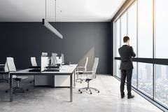 Businessman in bright office. Thoughtful young businessman standing in bright coworking office interior with furniture and daylight. Workplace concept royalty free stock image