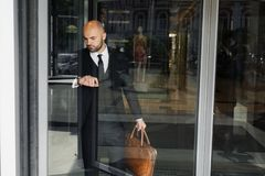Businessman with a brown bag near the office stock image