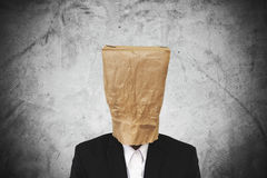 Businessman with brown paper bag on head, on dark concrete texture background Royalty Free Stock Photos