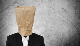Businessman with brown paper bag on head, on dark concrete texture background, with copy space Stock Photos