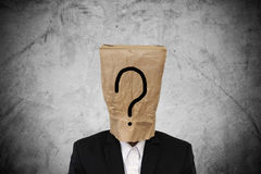 Businessman with brown paper bag on head, with question mark, on concrete texture background royalty free stock photography